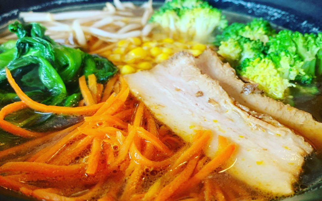 freshly made hot soba noodle soup with pork loin, carrots, greens, spinach, boy choi, broccoli and bean sprouts in soy sauce broth