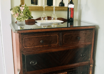 antique chest of drawers with red wine crystal glasses and flowers with gold mirror in bedroom