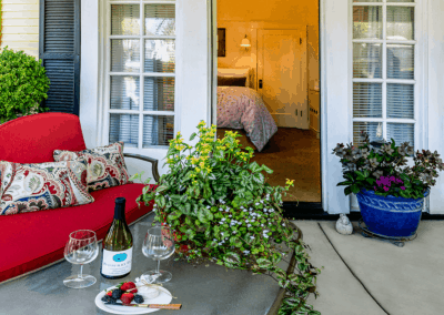 front porch seating with red couch floral throw pillows bayberry wine outdoor house plant cheese board with fresh fruit outside bedroom with queen bed