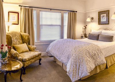 queen size bed with pale pink floral bedding and blue pillows a big oversized winged back chair oil painting and artwork antique furniture light pink walls and black out yellow curtains big window in bright room