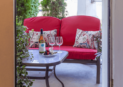 front porch seating with double couch floral throw pillows and crystal red wine glasses and bayberry wine on table with outdoor house plant