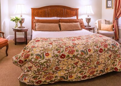 queen size bed with yellow floral bedspread silk pillows on antique bed with large brass lamps and wicker chair with cashmere throw and yellow down cushion
