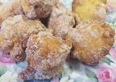 small donuts tossed in cinnamon sugar served as starter before breakfast on floral pink and green plate