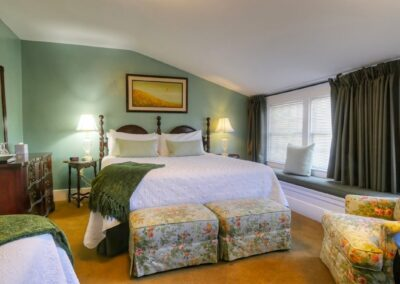 large king size bed in green room large window seatings in sunny room white bedding with pale green pillows oil painting and antique furniture in bed and breakfast