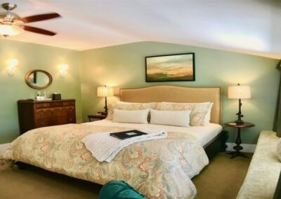 large california king bed in green room with ceiling fan antique furniture oil painting and art work beige bedding bird lamps in canterbury room of bayberry inn B&B