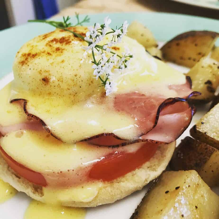 green plate with eggs Benedict with sliced gourmet ham topped with saffron hollandaise sauce and onion flowers served with side of roasted potatoes