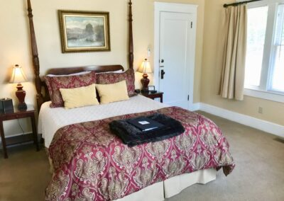queen bed with red and yellow pillows and cream bedspread bed has red wine in crystal and cookies served on tray oil painting and yellow room