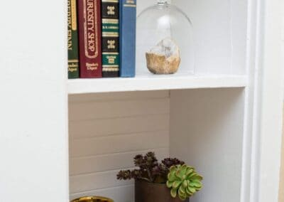 shelves in bedroom with antique books air plants, shell and vases as decor