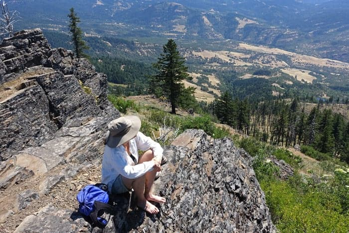 woman sitting on top of pilot rock